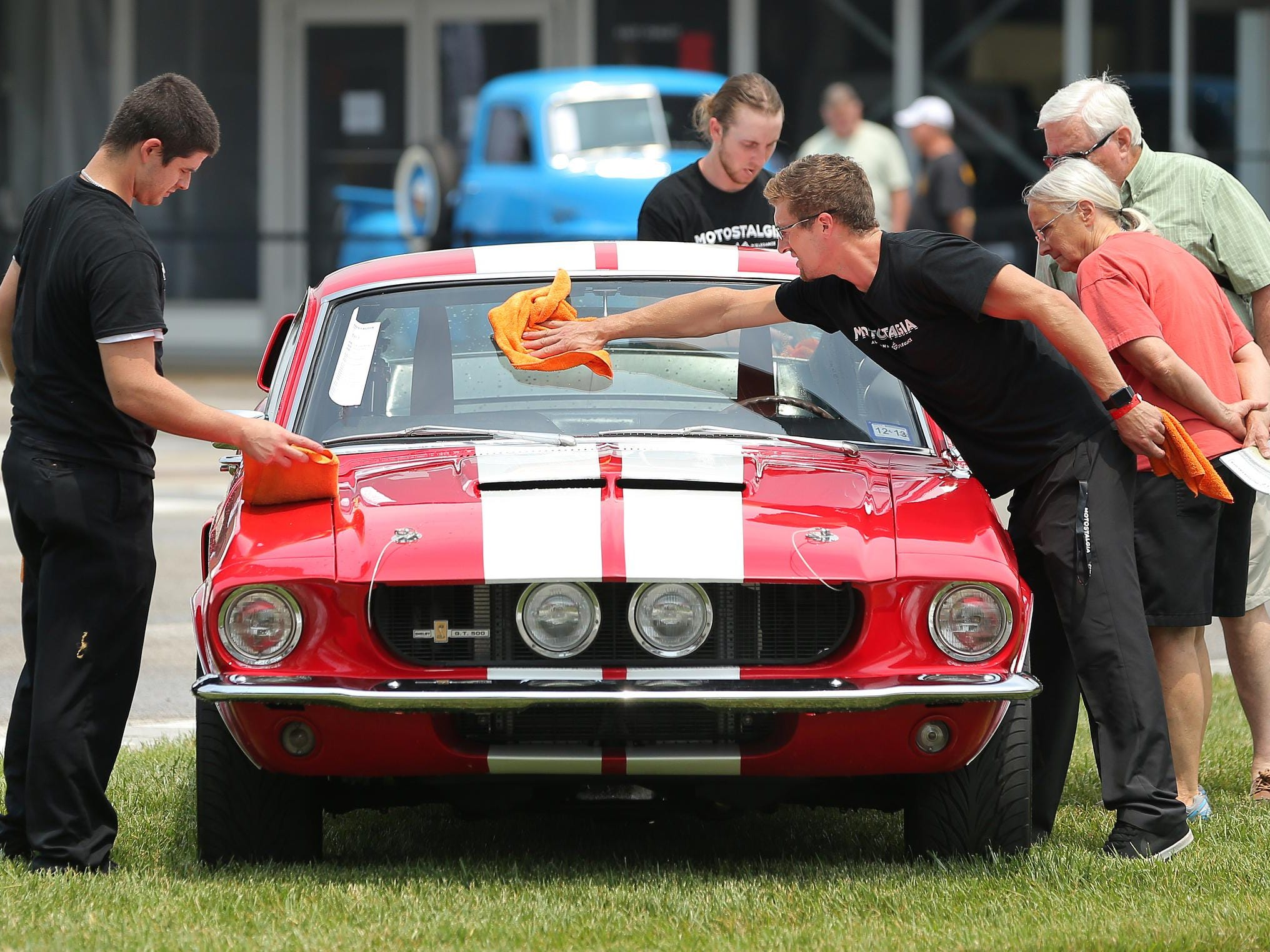 From left, owner Rick Vega, Tim Maggard and Addam Rodine with Jimmy Buffet's Auto Detailing out of Indianapolis wiped rainwater from a storm off of a 1968 Ford Mustang Fastback Shelby Tribute car. They were at the 2015 Brickyard Vintage Racing Invitational on Friday at Indianapolis Motor Speedway.
