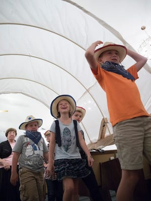 Students enjoy the Conestoga wagon cover they walk under as they leave for their individual Vacation Bible School lessons at Calvary Baptist Church Tuesday evening.