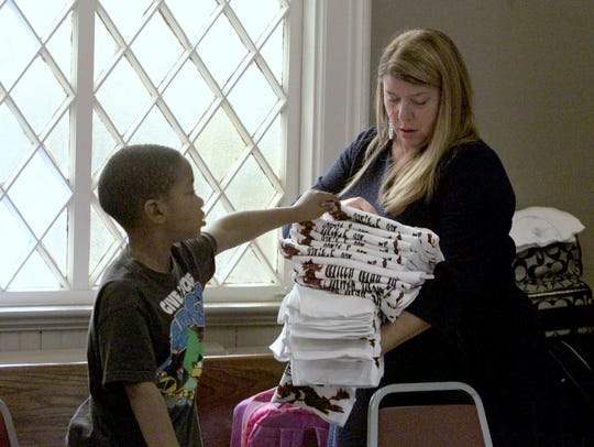 Director Kim Cross gives a shirt to Noble Whitted, 6, at the after-school program at the Nyack Center Nov. 25, 2014.