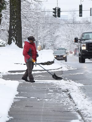 Rafael Ortiz of the Town of Poughkeepsie shovels away some snow on Route 9 in Hyde Park.