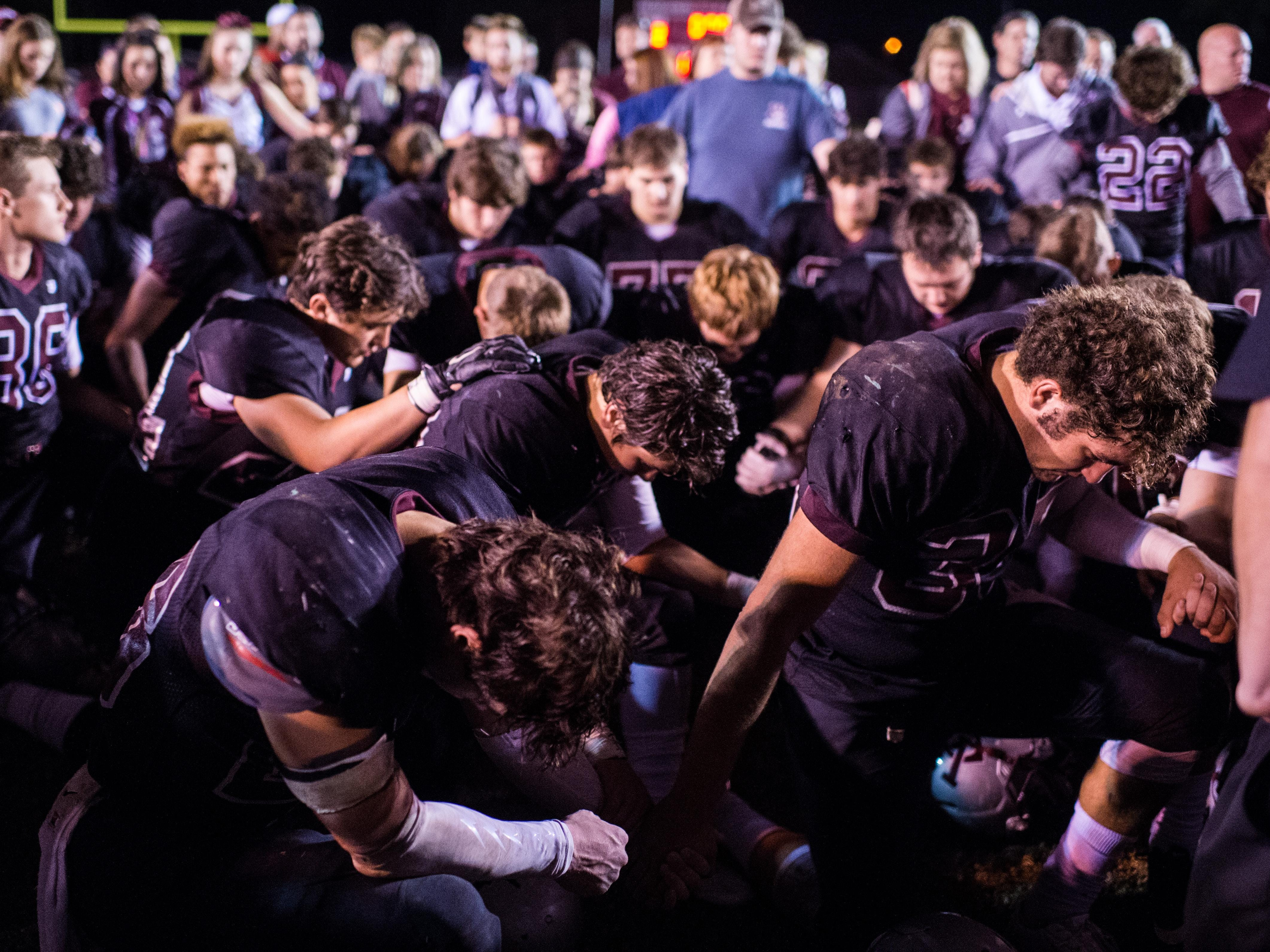 Vermilion Catholic players bow their heads in prayer following a 34-12 loss to Southern Lab in the semifinal round Friday.