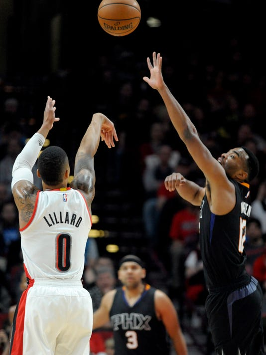 Portland Trail Blazers guard Damian Lillard hits a shot over Phoenix Suns forward TJ Warren during the first quarter of an NBA basketball game in Portland, Ore., Saturday, April 1, 2017. (AP Photo/Steve Dykes)