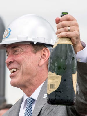 Craig Bouchard, chairman and CEO of Braidy Industries opens a bottle of champaign Friday, May 31, 2018, during a groundbreaking ceremony for Braidy Industries' 2.5 million square-foot, fully integrated aluminum rolling mill in Greenup, Ky.