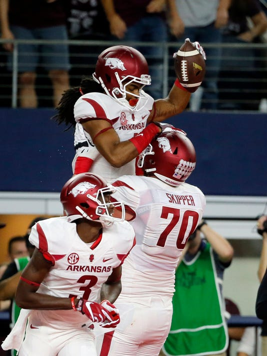 Arkansas wide receiver Dominique Reed (3) and offensive lineman Dan Skipper (70) celebrate with Keon Hatcher, top, after Hatcher caught a pass for a touchdown during the first half of an NCAA college football game against Texas A&M on Saturday, Sept. 24, 2016, in Arlington, Texas. (AP Photo/Tony Gutierrez)