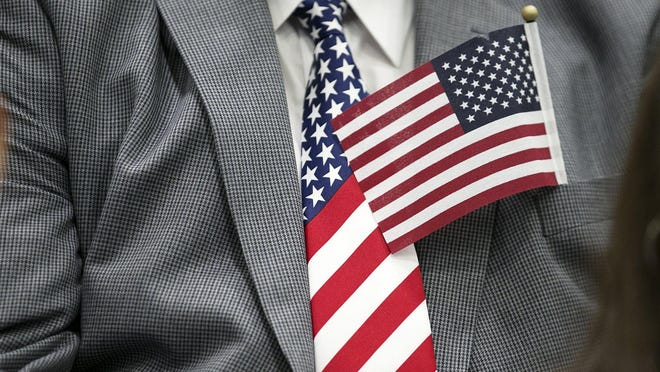 A man wears a U.S. flag tie as he waits to take the oath to become a citizen at a naturalization ceremony in Austin in 2016.