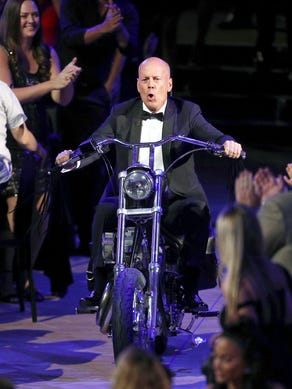 At least Bruce Willis looked cool before he felt the heat. On Saturday, the movie star entered his roast on a motorcycle, where he subjected himself to a number of jokes about his movies, personal life and appearance.