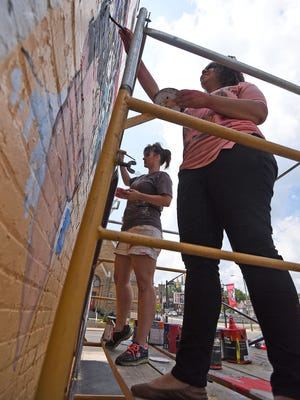 Robin Shoup and Ruthie Akuchie paint a mural on the side of the Fork and Fingers Restaurant on Wednesday.