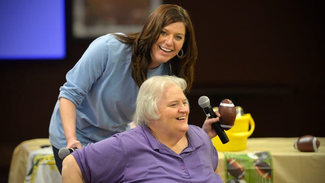 St. Benedict's Senior Community resident Jody Theis shares a laugh as they talk about the definition of a fumble with Recreation Coordinator Hilary Studenski, top, during a nursing home Super Bowl party Sunday, Feb. 7. The party included great game moments, famous commercials, food, and trivia.