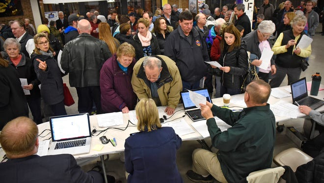 Caucus goers check in at a table near an entrance to Apollo High School during the Senate District 14 Republican Caucus in St. Cloud.