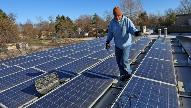 Dale Dashiell, with Rectify Solar, walks between solar panels during the job to install a second round of solar panels at St. Peter's United Church of Christ, Wednesday, Dec. 20, 2018.