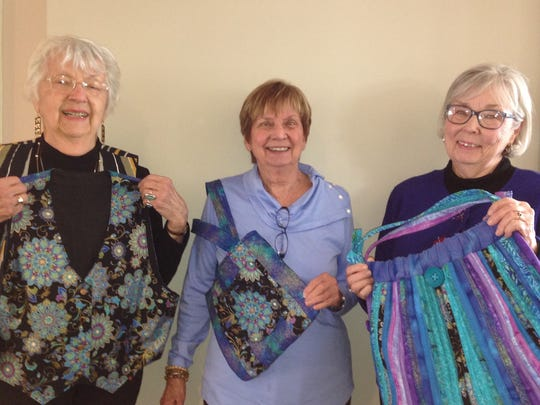 The members of the Quilting Queties were given three pieces of fabric and challenged to make something: (from left) Jean Smith shows her beautiful vest, June MacLennan wears her clever purse, and Ellen Pasieka shows her colorful tote bag. The members enjoyed seeing one another's creative projects.