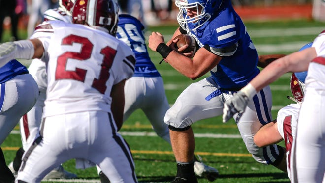 Grandville's Jalen Raniga defends against Novie Detroit Catholic Central's Cameron Ryan during CC's 28-14 win in the Division 1 regional final at Catholic Central Saturday.
