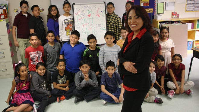 Arcelia Guillermo-Rios poses with her Desert Trail Elementary School students Friday in Chaparral. Guillermo-Rios was recently named Bilingual Teacher of the Year by the National Association for Bilingual Education.