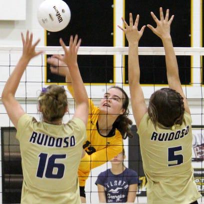 Alamogordo's Namika McCauley, center, tries to hit