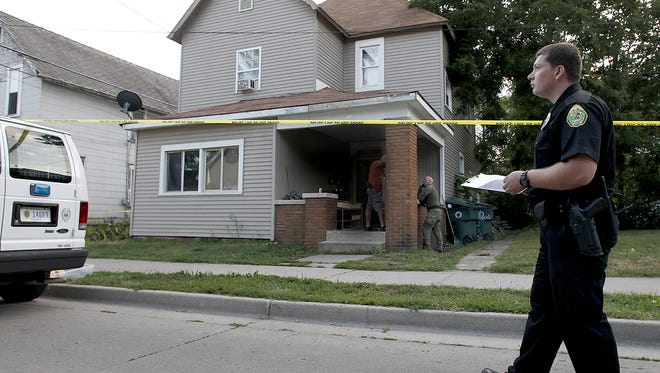 A Muncie Police Department officer monitors a house on Council Street in downtown Muncie in August 2014 during a search by police. A woman who was living in the house has won a lawsuit against the city and town of Albany over the search.