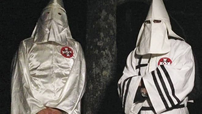 In this Dec. 2 photo, two masked Ku Klux Klansmen who declined to give their names,  stand on a muddy dirt road during an interview near Pelham, N.C. Generally speaking, wearing a hood or mask in public in North Carolina is illegal.