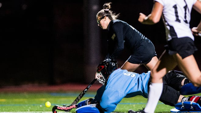 Palmyra's Lauren Wadas tries to get by a diving Warwick goaltender Catie Brubaker as Palmyra beat Warwick 3-2 in the first round of the PIAA District 3 tournament at Penn Manor's Comet Field on Wedensday, Oct. 25, 2017.