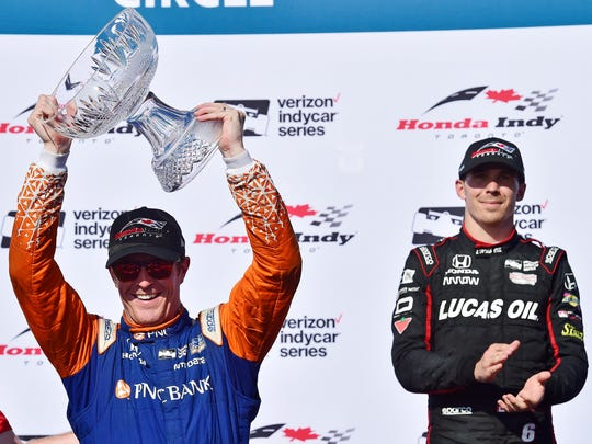 Scott Dixon, left, hoists the trophy after winning