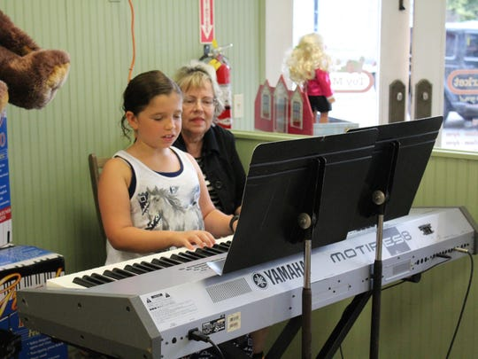 Kelley Crescenzo, 9, plays at the Toy Market, as her piano teacher, Cindy Birnbaun, look over her shoulder.