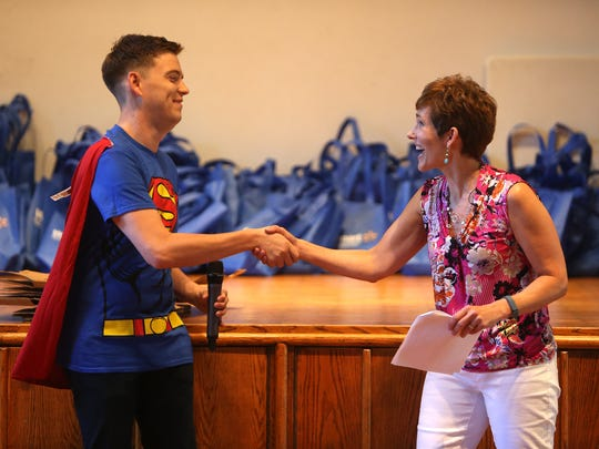 Community Soup Kitchen Community Educator Julie Hess thanks Joshua Stafford of Morristown dressed as Superman during a free 'Growing Healthy Kids' program for more than 100 local youngsters  thanks to a $42,000 grant from the Walmart Foundation held at St. Peter's Episcopal Church. August 3, 2016, Morristown, NJ