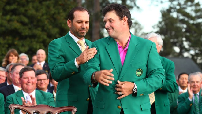 Sergio Garcia, the 2017 Masters winner, helps Patrick Reed into the green jacket after Reed won his first major.