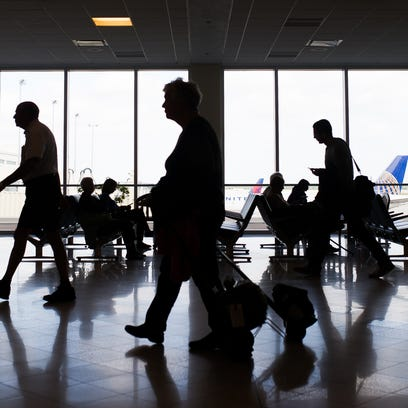 Travelers are seen walking through the terminal at
