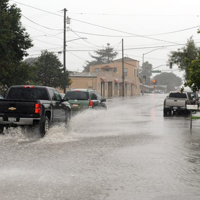 Cars negotiate flooded areas early Sunday morning at