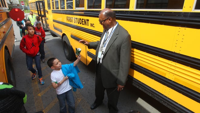 Larry Ellison, principal at School 33, helps students get to their buses at the end of the school day.