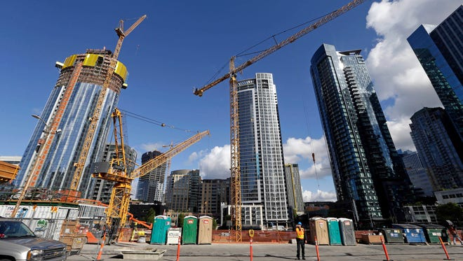 Construction cranes fill a block across from an Amazon building in Seattle in October 2017.