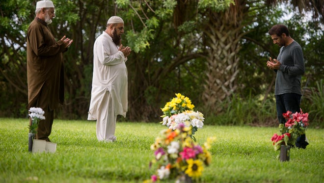 Tariq Hussain, of Vero Beach, who was 25 years old when he was murdered while working the register at his family-owned business in Lakewood Park, is buried at Hillcrest Memorial Gardens in St. Lucie County. His mother, Khurshid Hussain, died after him and is buried nearby. Tariq's brother, Ozzie Hussain (center), said he and their father, Nazer Hussain (left), visit weekly to pray at the grave sites. Another brother, Talat Hussain, who was visiting from out of town, prays with them Aug. 11, 2017.
