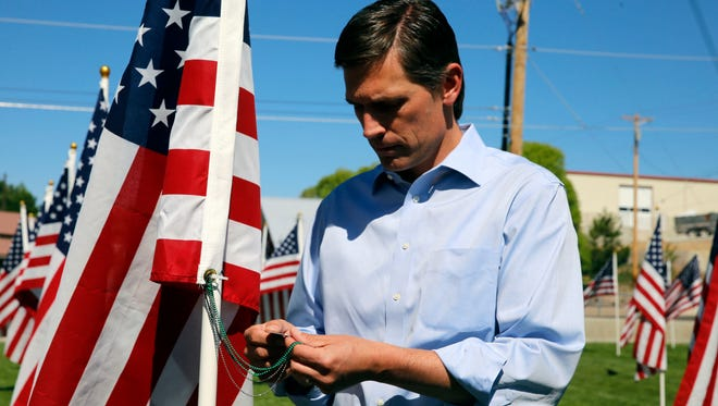 Sen. Martin Heinrich, D-NM, looks at a dog tag on a flag Monday, May 30, 2017, at the Healing Field in Farmington.