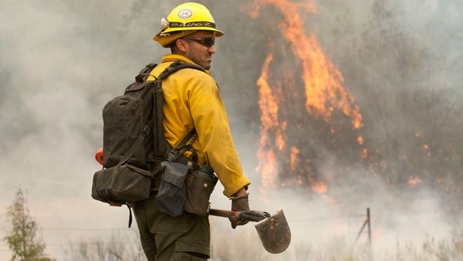 A hotshot sets a burn-out fire along Highway 191 to protect the town of Nutrioso, Arizona, from the Wallow Fire in 2011.