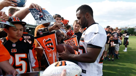 Cincinnati Bengals halfback Giovani Bernard signs autographs for fans after practice at training camp downtown.