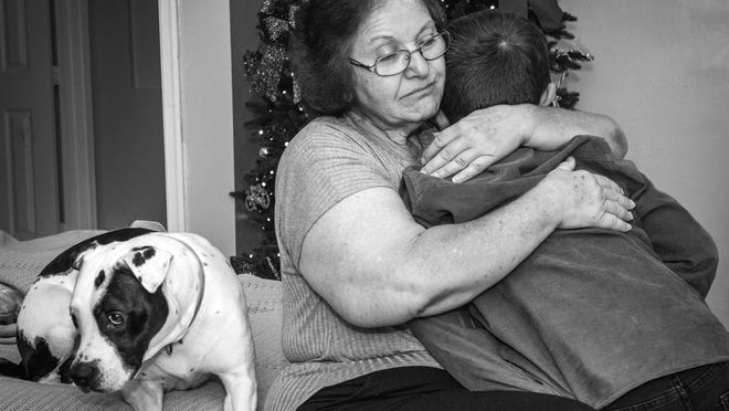 Maryann Jackrel holds her 5-year-old grandson Alyjah while the family dog Spot sits nearby.