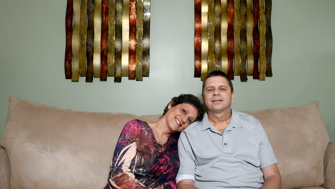 Jim and Lisa Fox sit on their living room couch Thursday, March 12 at their home in Charlotte. Both are battling cancer.