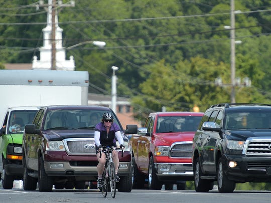 KJ Garner rides her bike from East Nashville to her job at REI in Brentwood on Friday, Aug. 26, 2016.  Garner crosses the busy intersection of Franklin Road and Old Hickory Blvd in Brentwood on Friday, Aug. 26, 2016.