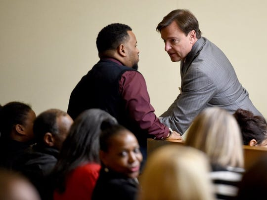 Attorney Greg Isaacs, right, talks with his client