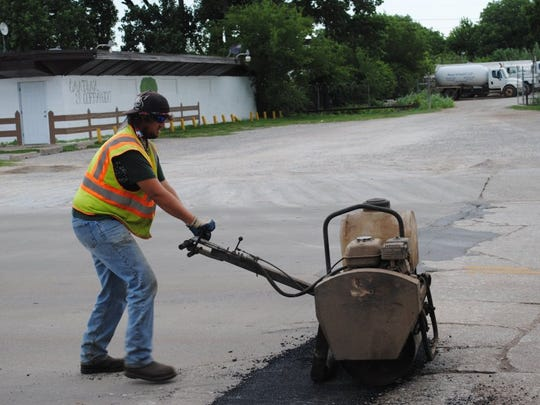 In this file photo, City of Wichita Falls employee Jesse Harris uses a heavy roller to pack down asphalt into a pothole on Scott Avenue. The city recently announced requests for proposal on two major street rehabilitation projects including asphalt improvements and seal coat projects.