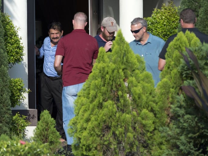 A man at the door of a home in the of 500 block of SW Bayshore Blvd. is seen escorting out local and federal investigators Sunday at the Port St. Lucie home. After searching the property in the 900 block of SW Bayshore Blvd., the law enforcement officers moved their efforts to the second home. Both are connected to Orlando nightclub shooter Omar Mateen.