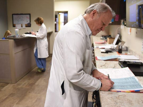 Dr. Craig Towers makes notes between seeing patients from his practice at High Risk Obstetrical Consultants on Feb. 23.
