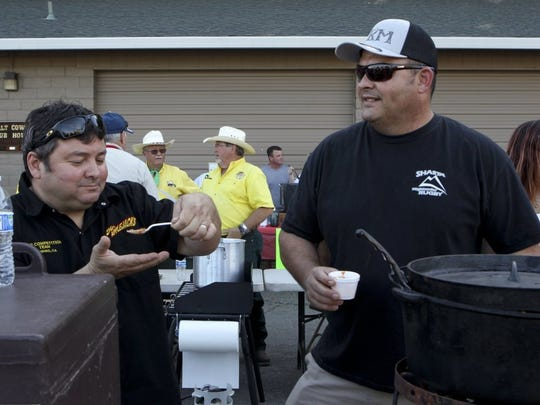 In May 2016, David Duarte (left) of Mr. AppleJacks tastes a spoonful of the chili prepared by Andreas Mittry (right) of Mittry Brothers Chili. A baker's dozen of cooks competed in the annual chili cookoff that year.