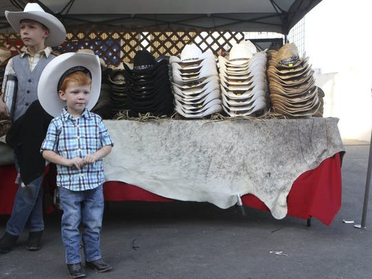 Bradan Moon, 9, (left) and his 3-year-old brother Cooper Moon wait to enter the 2016 Redding Rodeo after their parents bought them cowboy hats.