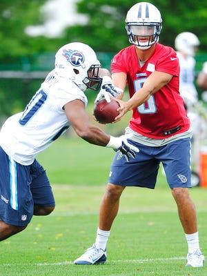 Quarterback Marcus Mariota (8) hands off to Bishop Sankey (20) during Titans practice on Tuesday.