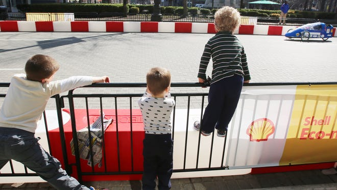 Gino Gisevan, 6, of St. Clair Shores left, Dominic Mazzocco, 2, center,  of Clawson and Julian Gisevan, 3, of St. Clair Shores are excited as they watch cars zoom by in downtown Detroit during a race that is  part of the Shell Eco-Marathon Americas competition on  April 12 .