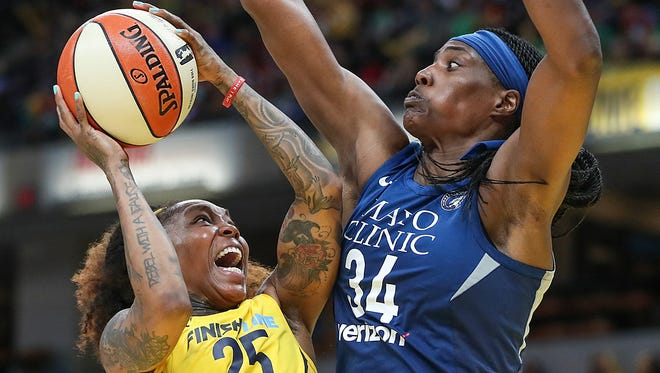 Indiana Fever guard Cappie Pondexter (25) takes a shot past Minnesota Lynx center Sylvia Fowles (34) after being fouled, during second half action at Banker's Life Fieldhouse in Indianapolis, Wednesday, July 11, 2018. The Fever lost to the Lynx, 87-65.