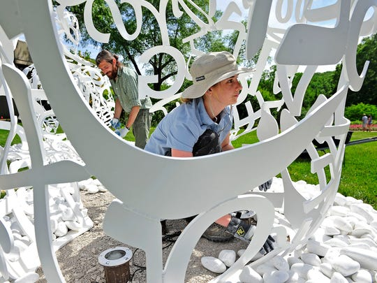 """Jordi Ayuso Llull, left, and Jane Coleman Harbison work on installing """"The Soul of Words"""" I and II for the Jaume Plensa exhibition at Cheekwood opening on Friday."""