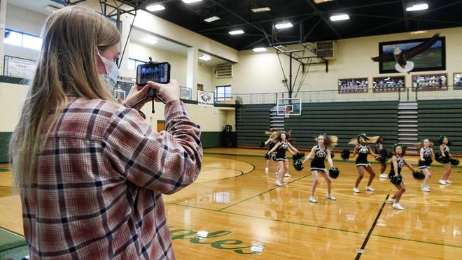 """Delaney Jackson films East Henderson High cheerleaders on Instagram Live for a virtual pep rally Friday. """"It was stressful but in a good way,"""" said Jackson of the behind-the-scenes directing, """"We worked really hard on it."""""""