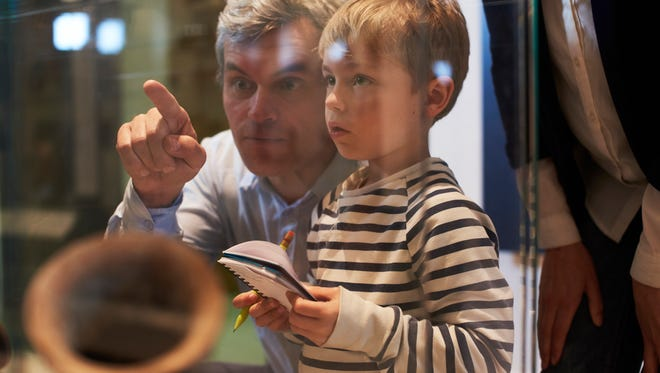 Father And Son Look At Artifacts In Case On Trip To Museum