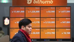A man passes by a screen showing the prices of bitcoin
