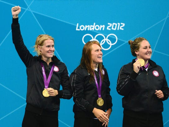 From left, Betsey Armstrong, Heather Petri and Melissa Seidemann celebrate Team USA's gold medal in women's water polo at the London 2012 Olympic Games on August 9, 2012.
